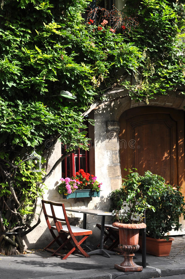 European Countryside Setting. A relaxing, cosy, provencal spot outside a cafe restaurant surrounded by plants and shrub on a street in Paris, France stock photography