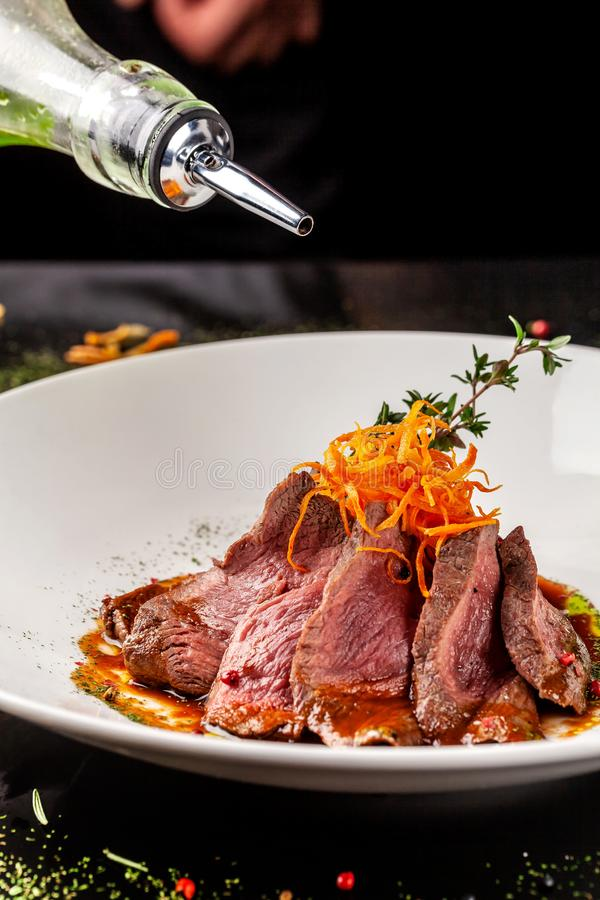 European cuisine. Marinated veal with roast Medium rare. Degree of roasting. Chef pours beef olive oil. Serving dishes. In restaurant in a white plate stock photo