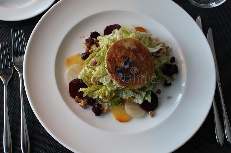 Restaurant goat cheese salad with beetroot and cranberries. European cuisine restaurant goat cheese salat with tricolor beetroot, cranberries and wallnut royalty free stock photography