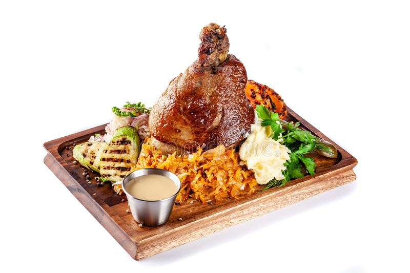 European, Czech cuisine. Pork knuckle on a wooden board with mashed potatoes, stewed cabbage, grilled vegetables and suck royalty free stock images