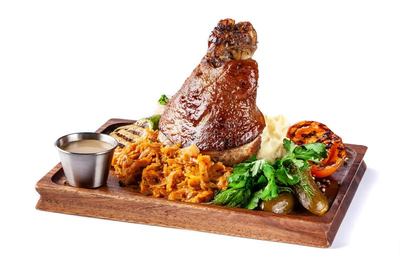 European, Czech cuisine. Pork knuckle on a wooden board with mashed potatoes, stewed cabbage, grilled vegetables and suck stock photo