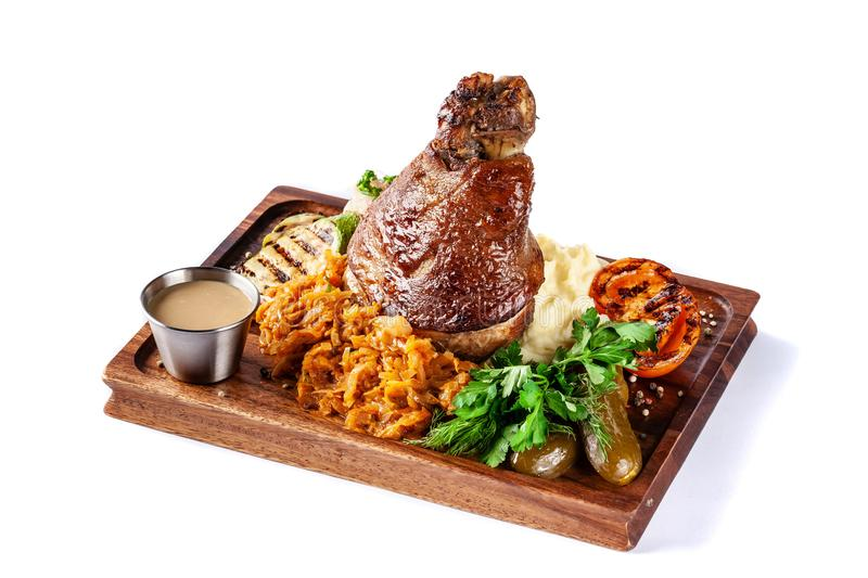 European, Czech cuisine. Pork knuckle on a wooden board with mashed potatoes, stewed cabbage, grilled vegetables and suck royalty free stock photo