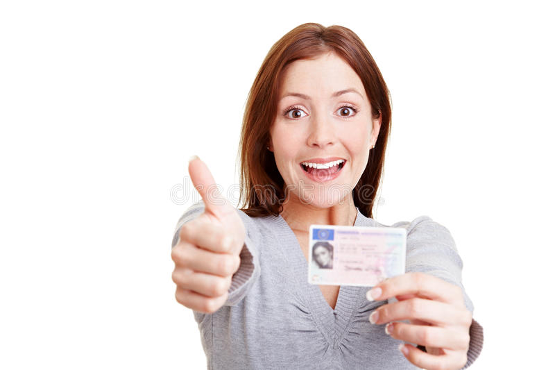 European drivers license. Happy woman with European driving license holding her thumbs up stock photo