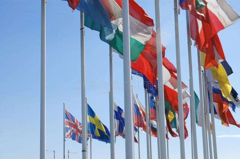 European flags in the wind. Flags of European states against blue sky stock photos
