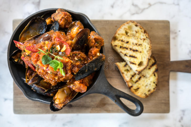 European Food: Blue mussel baked in tomato sauce stock photos