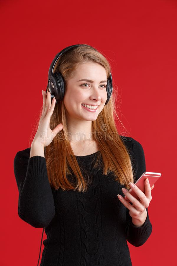 European girl in black headphones and holding a smartphone in her hand and smiling. On a red background. stock photos