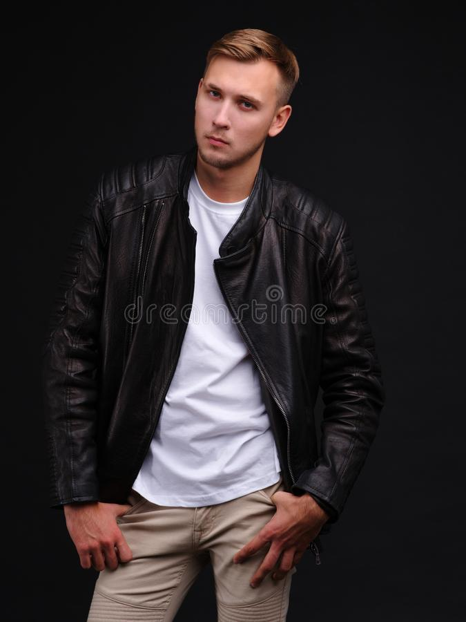 European guy in a jacket poses standing with a serious piercing gaze. stock photos