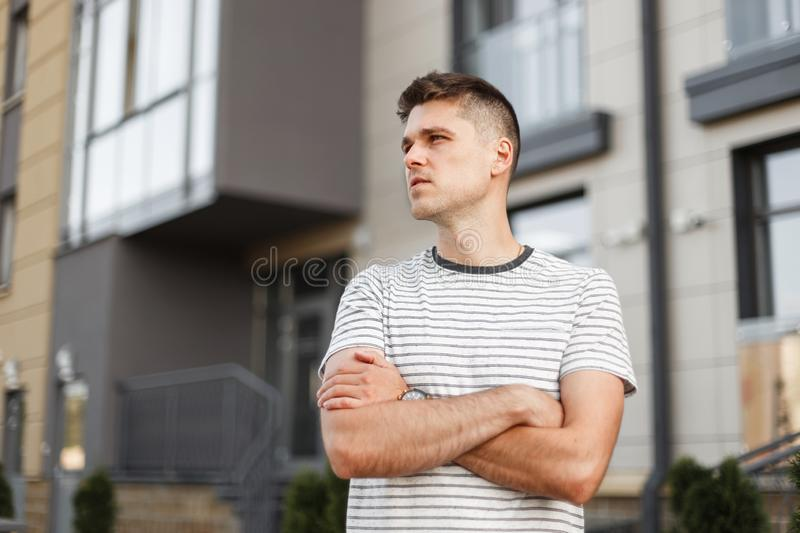 European handsome young man with trendy hairstyle in a trendy striped t-shirt posing in the city near the building. Handsome guy royalty free stock photography