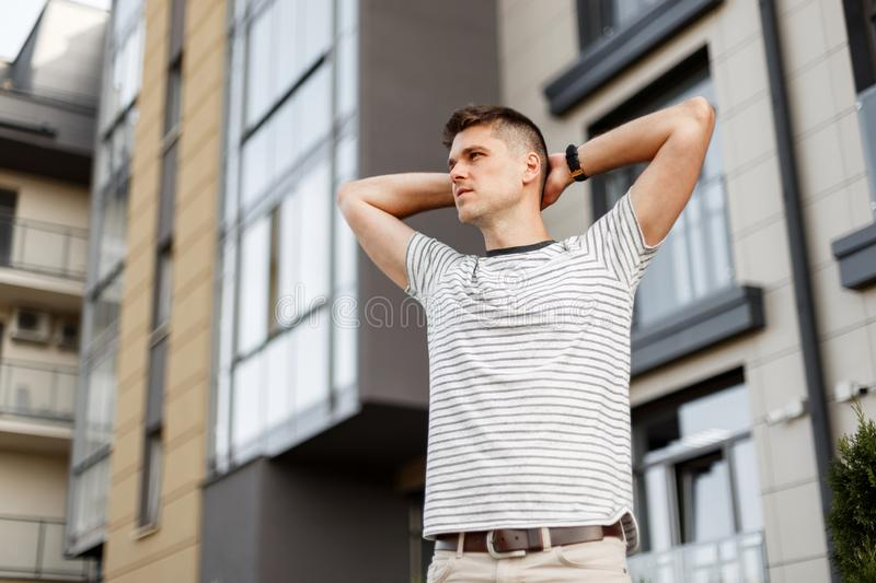 European handsome young man with trendy hairstyle in a trendy striped t-shirt posing in the city near the building. Handsome guy stock images