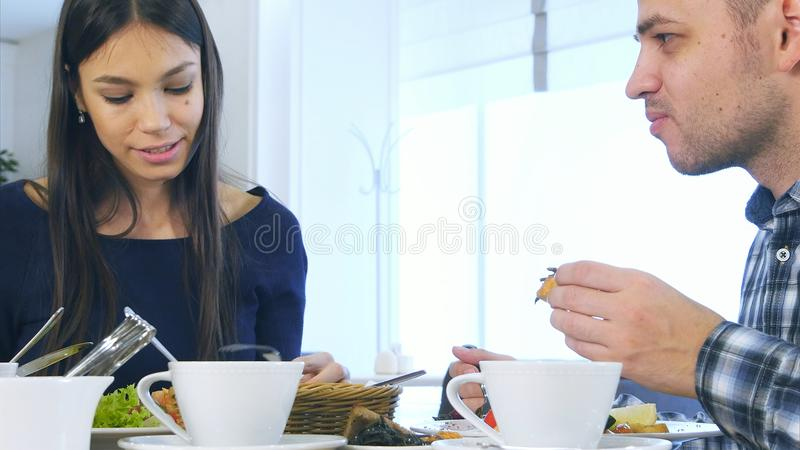 European harmonious family have healthy lunch in cafe. They eating vegetable salad, chatting and smiling. royalty free stock image