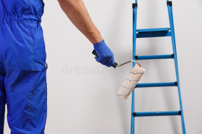 A male worker painter, in a blue uniform and gloves holding a platen. Standing opposite the wall with a stepladder. stock images