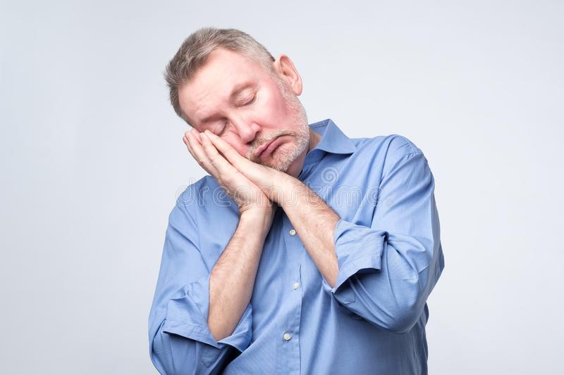 European man in blue shirt being tired sleeping on hands. stock images