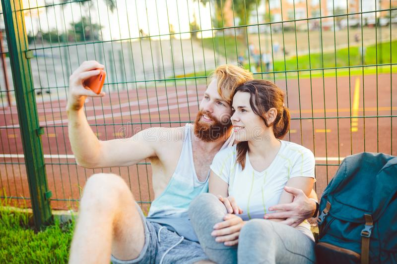 A European man`s pair of red hair and a beard and a woman rest after playing sports outdoors. The guy holds a red stock photography