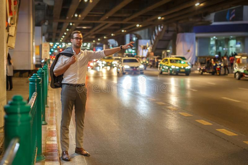 European man stops a taxi on the street of Bangkok in Thailand stock photography