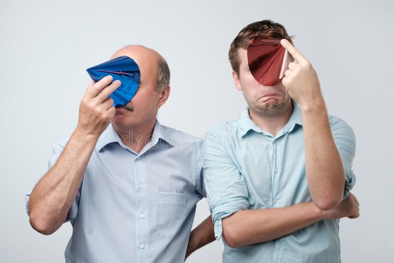 Mature father and son hiding their face with birthday cap after great party having hangover. European mature father and son hiding their face with birthday cap stock photo