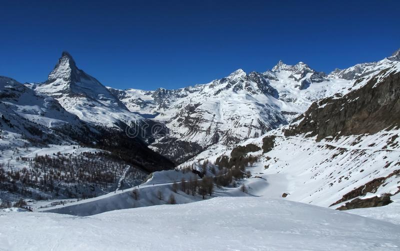 European mountains landscape, Alps, Italy, mountain skiing resort, picturesque view with deep blue sky, high rock peaks on horizon. Forest trees, white ice stock images