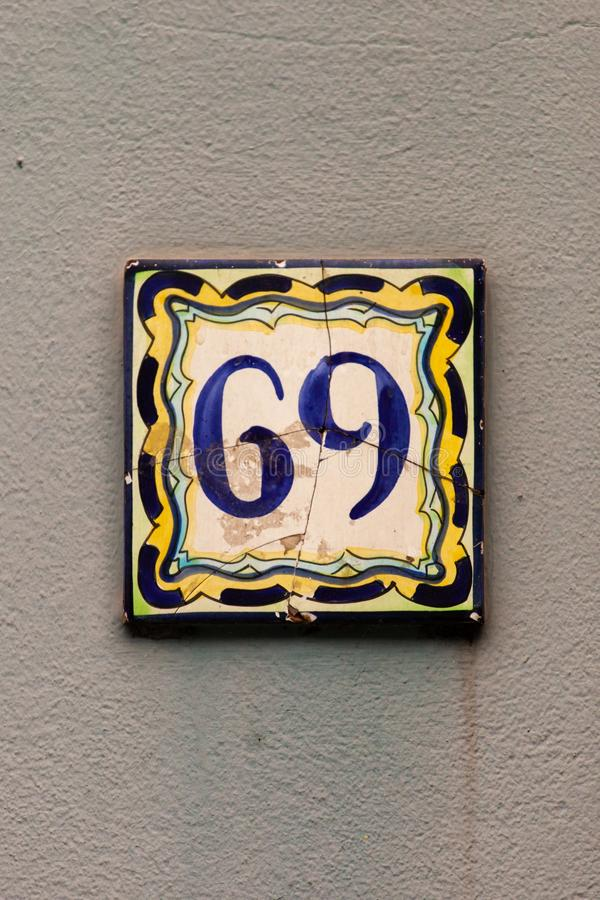 Number 69 antique hand painted ceramic sign house number on gray wall royalty free stock image