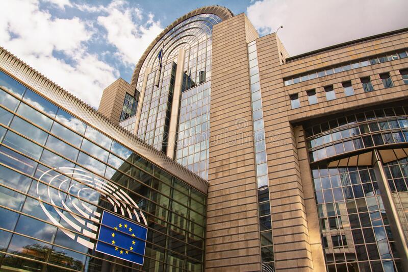 European Parliament building in Brussels. With a european flag and  reflections of sky and surrounding buildings stock photos