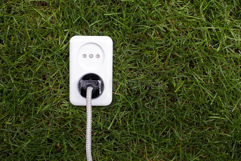 European power socket on grass. Energy concept stock photos