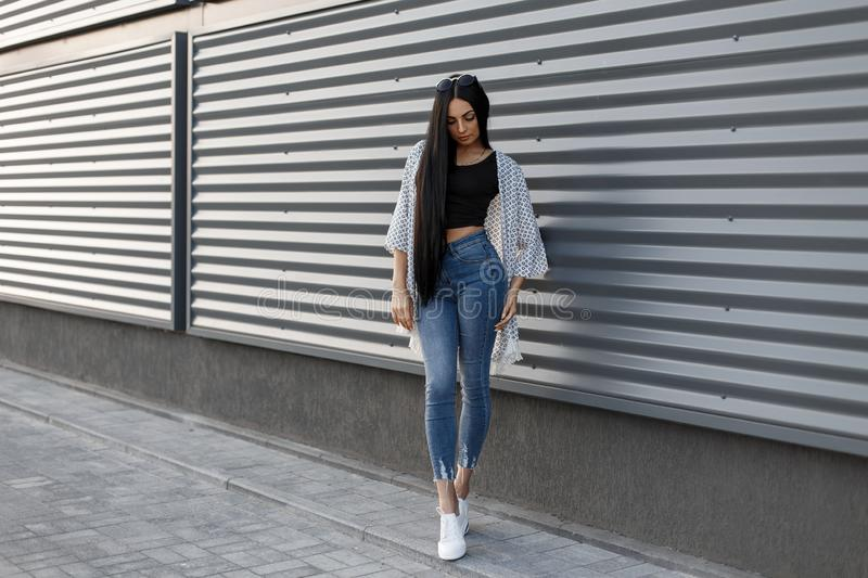 European pretty young stylish woman with gorgeous long hair in fashionable summer clothes is standing near the modern metal wall stock photos