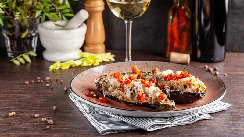 European Spanish cuisine. Baked eggplants with meat and vegetables, parmesan cheese. White wine on the table. Close-up background royalty free stock photography