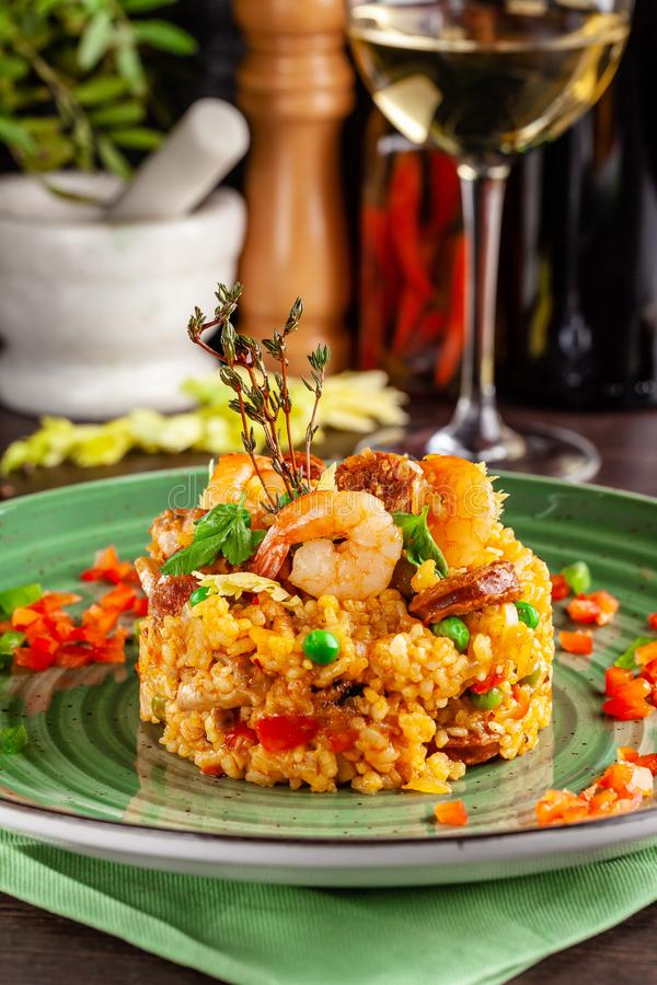 European Spanish cuisine. Paella with shrimps, chicken and coblas chorizo. White wine on the table. Closeup background image stock image