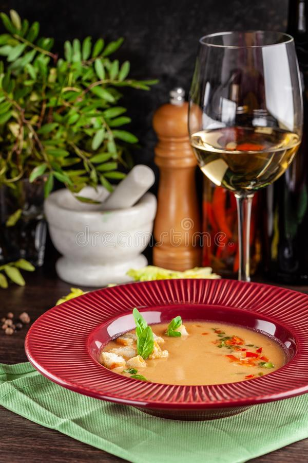 European Spanish cuisine. Summer tomato soup Gospacho with crackers, and vegetables. White wine on the table. Close-up background royalty free stock photo