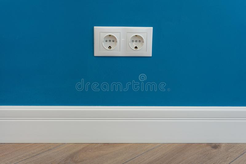 European standard 220 volt wall electrical outlet on wall with baseboard and hardwood floor stock photography