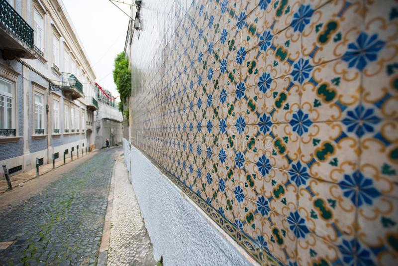 European street with old wall with traditional Portuguese decor tiles azulezhu in blue,yellow and brown tones. stock photos