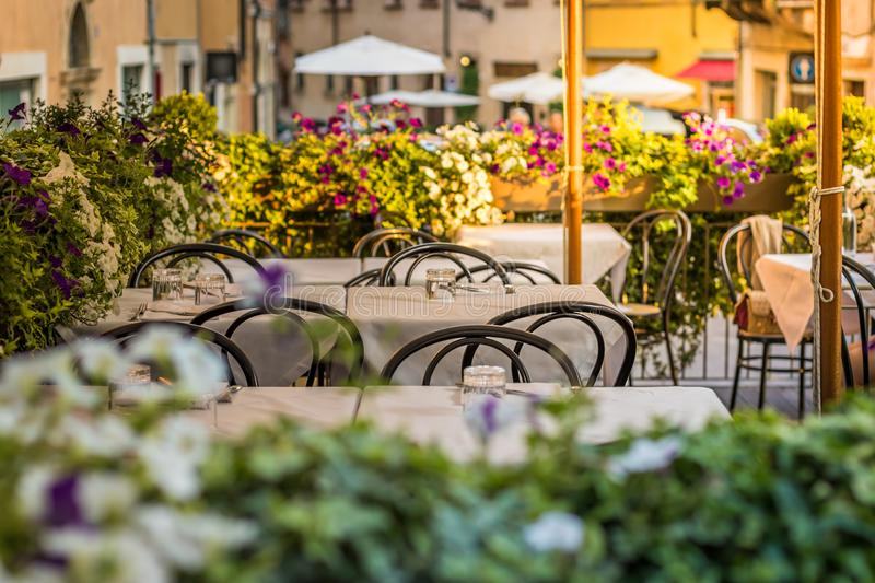 European street restaurant or cafe. Tables with white tablecloths outdoors royalty free stock images
