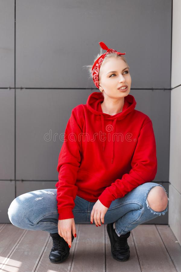 European stylish young blond woman in a fashionable red hooded sweatshirt in a vintage bandana in black boots in a blue jeans. Is sitting near a gray building royalty free stock images