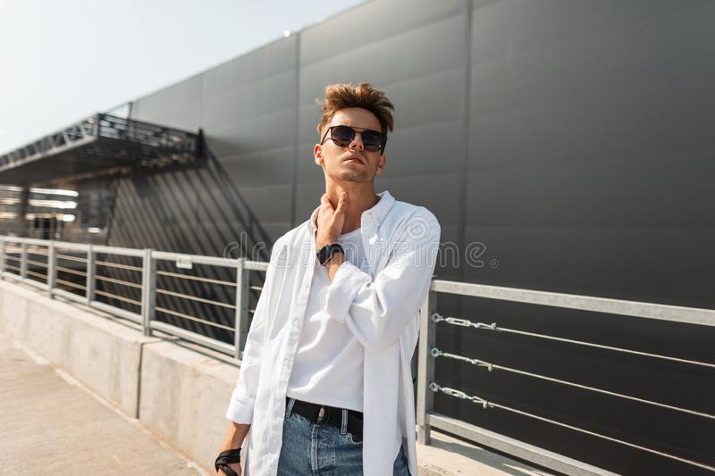 European stylish young hipster man in fashionable summer clothes in black sunglasses with a fashionable hairstyle stands. On the street on a sunny day royalty free stock images