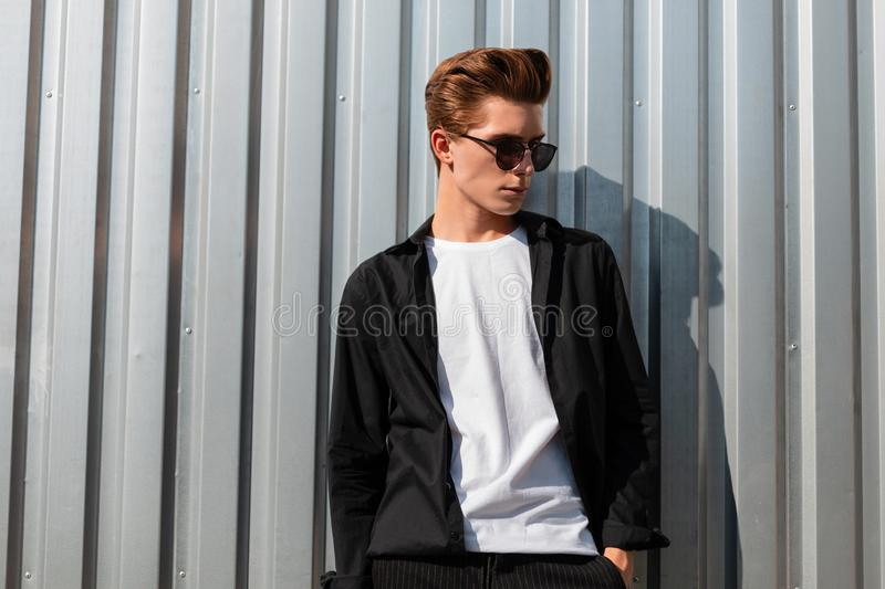 European stylish young man with a trendy hairstyle in elegant clothes in fashionable sunglasses poses near a shiny metal wall. In the city on a sunny day royalty free stock photo