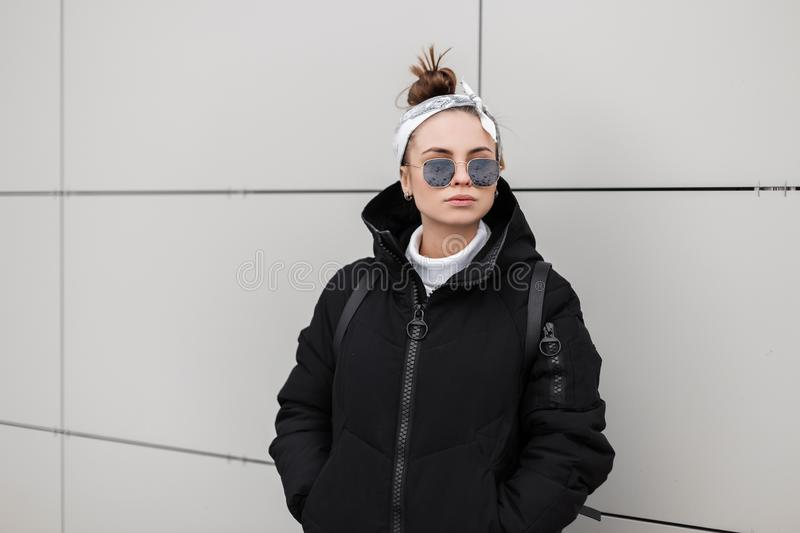 European stylish young woman hipster in fashionable black coat with a fashionable hairstyle with a stylish bandana. Posing in the city near a white wall. Women` royalty free stock photography