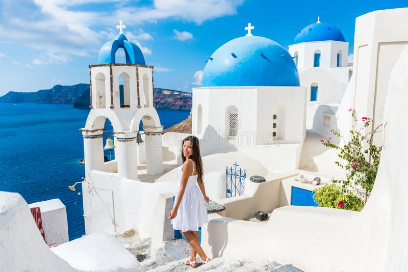 European summer vacation girl walking at Oia domes. Santorini travel tourist woman on vacation in Oia walking on stairs. Lovely girl in white dress visiting the royalty free stock photo