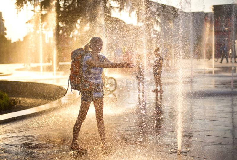 European tourist with back pack. Water splashes in sunset royalty free stock images
