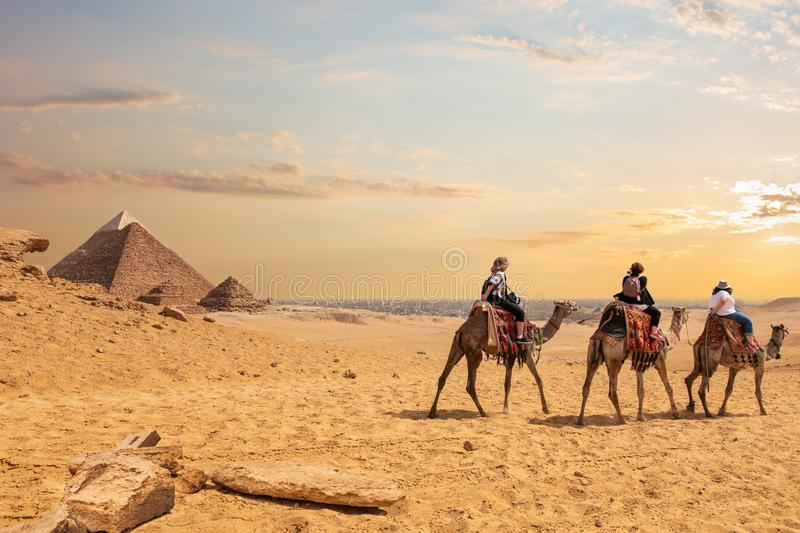European tourists riding camels near the Pyramids of Egypt royalty free stock photo