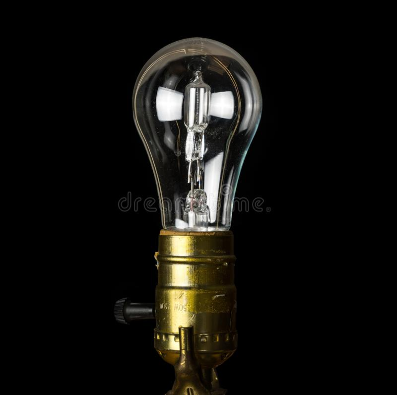 Brass light holder with a halogen lightbulb soon to be banned in EU. The European Union is banning the sale and manufacture of halogen light bulbs because they royalty free stock photo