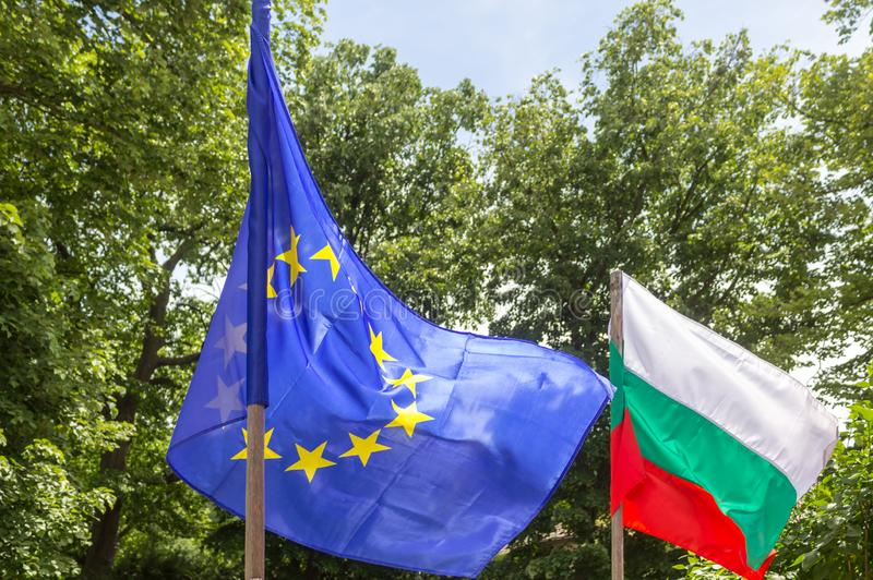 European Union and Bulgaria flag waving in the wind, trees behind.  Diplomacy concept, international relations.  stock images