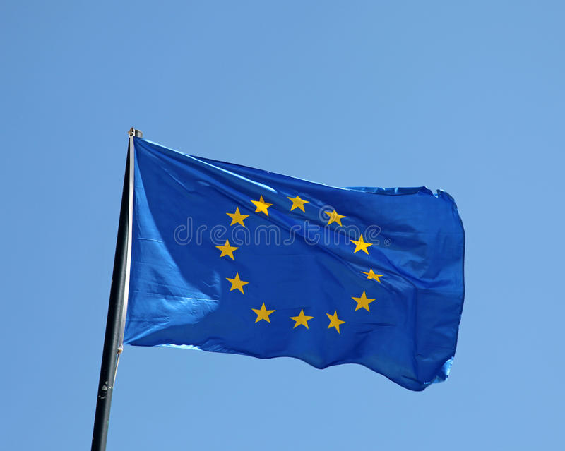 European Union Flag. An European Union flag flying in the wind with blue sky background royalty free stock photography