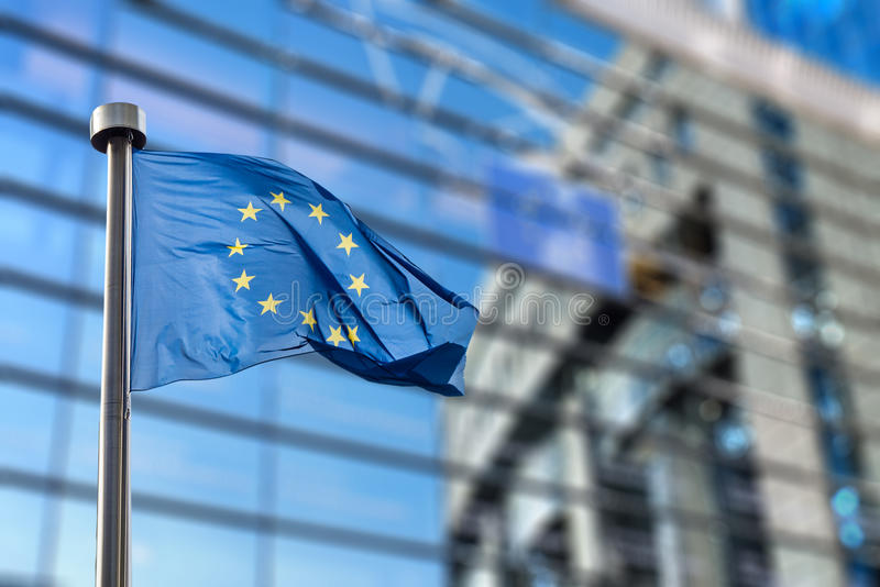 European Union flag against European Parliament. European Union flags in front of the blurred European Parliament in Brussels, Belgium royalty free stock image