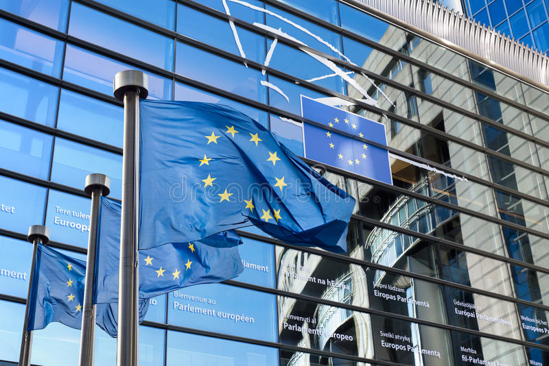 European Union flag against European Parliament. European Union flags in front of the European Parliament in Brussels, Belgium royalty free stock images