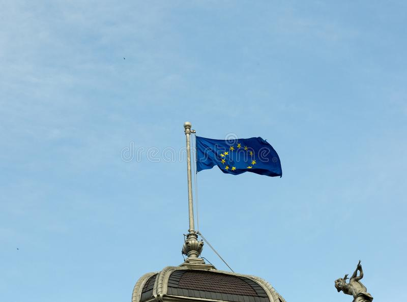 European Union flag at the top of the building. European Union flag at the top of the old building with angel sculpture stock photos