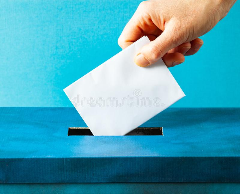 European Union parliament election concept - hand putting ballot in blue election box. Politics, referendum, vote, democracy, voting, government, background royalty free stock images