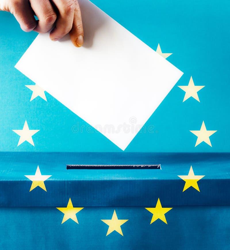 European Union parliament election concept - hand putting ballot in blue election box - EU flag. Politics, referendum, vote, democracy, voting, government stock photo