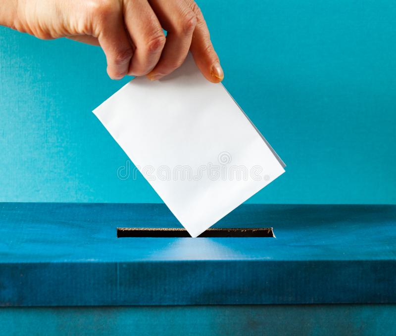 European Union parliament election concept - hand putting ballot in blue election box. Politics, referendum, vote, democracy, voting, government, background royalty free stock photo