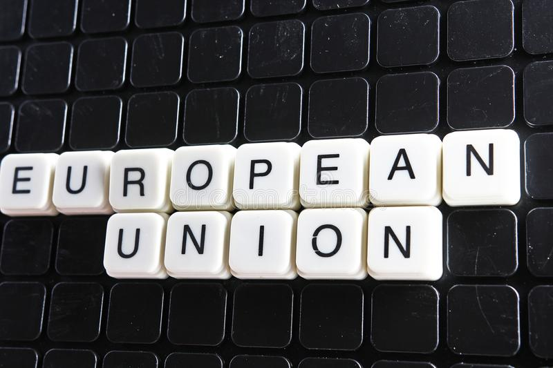 European union title text word crossword. Alphabet letter blocks game texture background. White alphabetical letters on. Black background. White educational toy royalty free stock photography