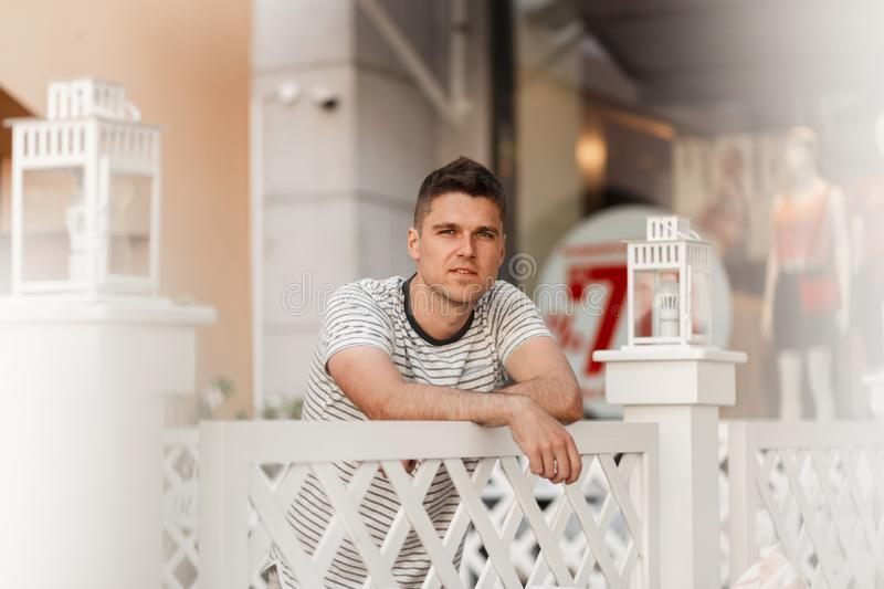 European urban young man in a fashionable striped t-shirt with a cute smile stands near a vintage wooden fence on the terrace stock images