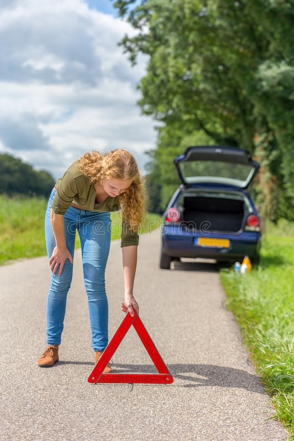 European woman placing hazard warning triangle on road royalty free stock photos