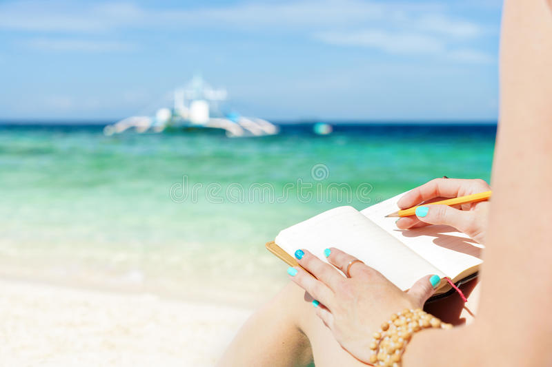 European woman is sitting on the coast of tropical turquoise sea and wrigting by pen in notepad at sunny summer day royalty free stock photos